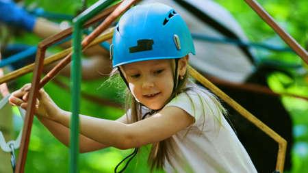 Rope adventure - smiling girl in helmet crossing the rope bridge