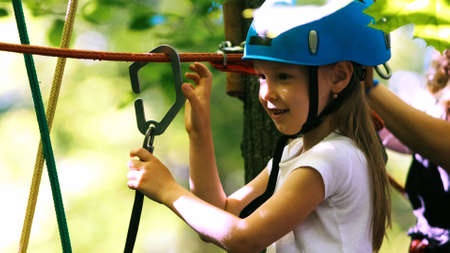 Rope adventure - a girl with an insurance hook attached to the rope crossing the rope bridge Standard-Bild