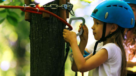 Rope adventure - a girl attaching an insurance hook to the rope Standard-Bild