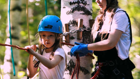 Young woman and her daughter crossing the rope bridge on an attraction in the park