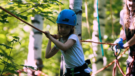 Rope adventure - a girl with an insurance hook attached to the rope walking on rope bridge Standard-Bild