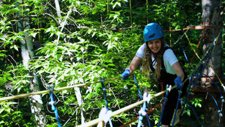 Rope adventure in forest - smiling woman walks on the rope bridge
