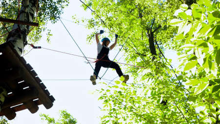 Rope adventure in forest - woman walks on ropes Standard-Bild