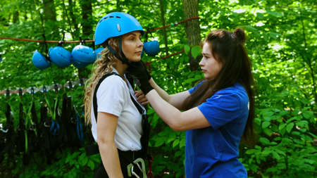 A young woman instructor puts on the helmet pendants on a woman Standard-Bild