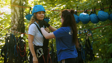A young woman instructor putting a helmet on a head of the woman Standard-Bild