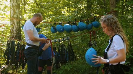 Extreme rope adventure - a couple putting on their insurance Standard-Bild