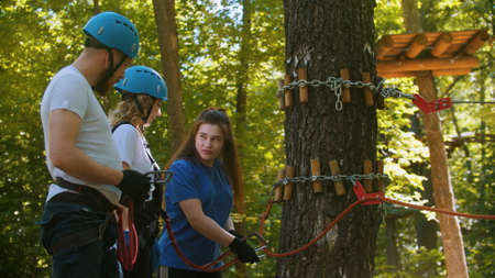 Extreme rope adventure - instructor explaining to a couple how to use their insurance hooks