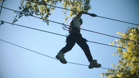Rope adventure - slim woman walks on the suspension rope bridge Standard-Bild