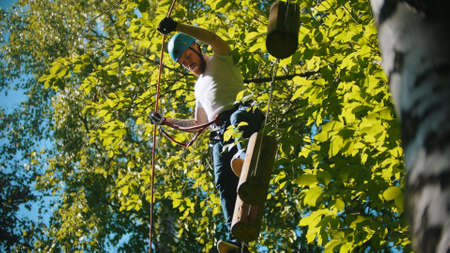 Man crossing a construction of the rope and stumps - an entertainment attraction in the forest Standard-Bild