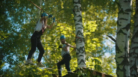 Man and woman crossing the rope bridge - an entertainment attraction in the green forest Standard-Bild