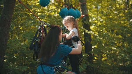 Woman instructor helping a little girl putting on the insurance belt Standard-Bild