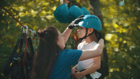 Rope adventure - woman instructor helping a little girl putting on helmet
