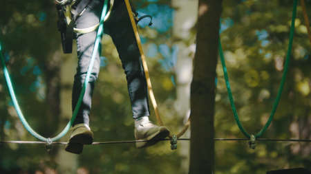 A girl walking on the rope in forest