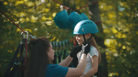 Woman instructor helping a little girl putting on helmet