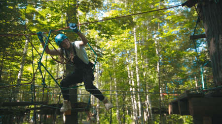 Woman crossing a rope bridge - an entertainment attraction in the forest Standard-Bild