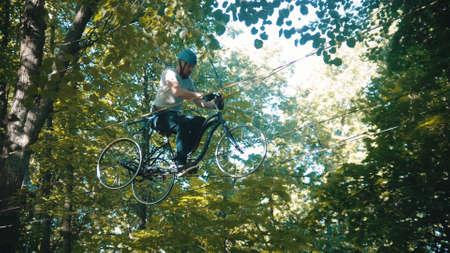 Man crossing the rope bridge on the bike
