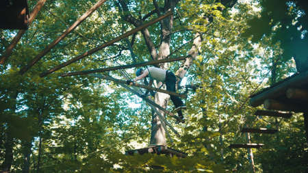 A man crossing rope construction in the forest - extreme attraction Standard-Bild