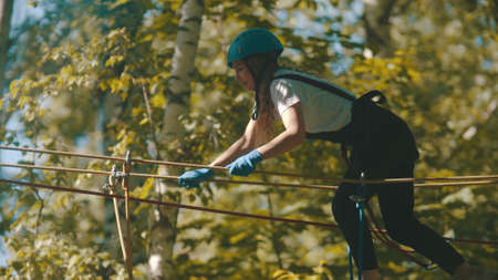 A woman in helmet crossing the rope bridge - an entertainment attraction in the forest