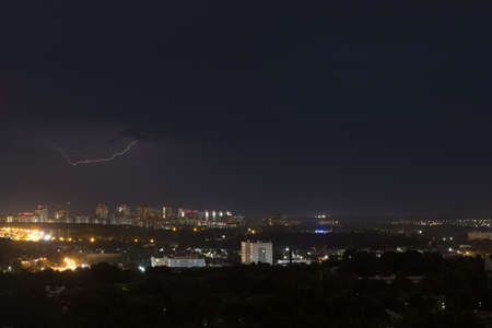 Lightning flashes in the night cloudy sky above the city
