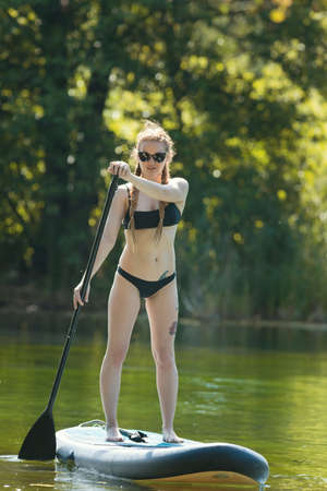 Rafting - young woman in black swimsuit standing on swimming raft