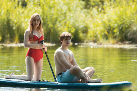 Rafting - young woman in red swimsuit and man standing on the raft by the river and holding paddle Banque d'images