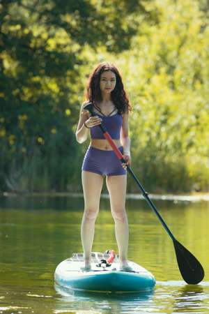 Rafting - young woman in purple swimsuit standing on swimming raft and holding a paddle