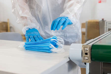Industrial production of protective medical masks - worker in protective gloves packs the masks together