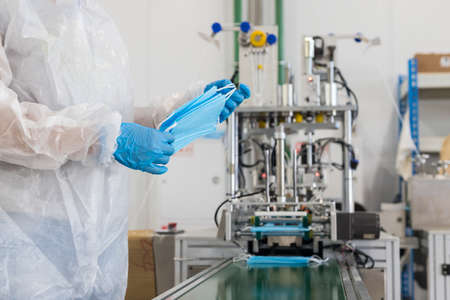 Industrial production of protective medical masks - worker packs the masks together