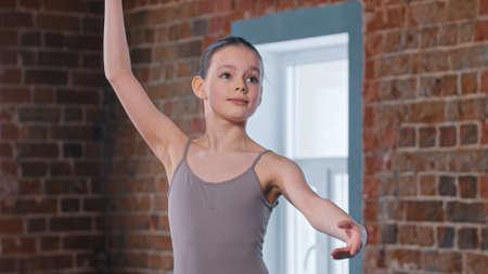A little pretty ballerina girl training movements in the studio Foto de archivo
