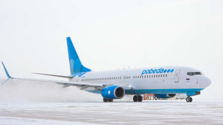 10-02-2021 KAZAN, RUSSIA, Kazan International Airport : a white and blue plane from POBEDA campaign on airport runway field