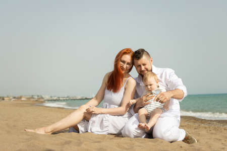 Happy family on vacation sitting on a sand beach with a baby son