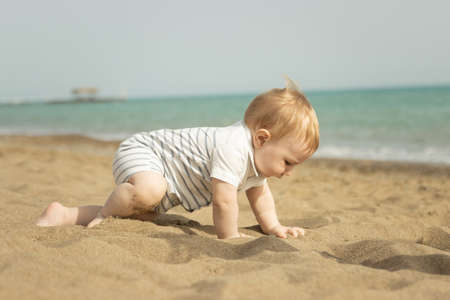 A baby boy crawling on a sand on the seaside