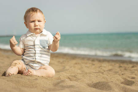 A baby boy sitting on a sand on the seaside