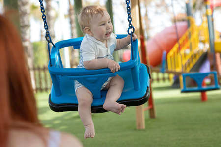 A little boy on swings on an outside playground Stock Photo