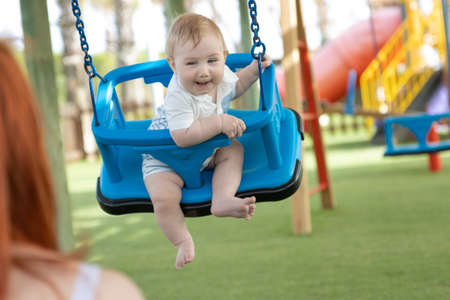 A little funny boy on swings on an outside playground