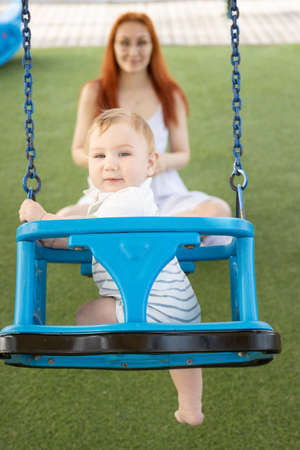 A little boy on swings on an outside playground with his ginger mother - looking in the camera