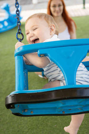 A little laughing boy on swings on an outside playground with his ginger mother - looking in the camera Stock Photo