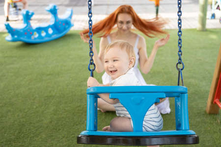 A little laughing boy on swings on an outside playground with his ginger mother