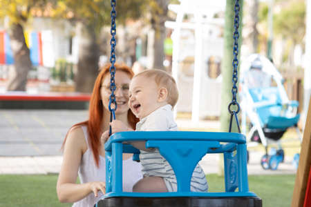Happy family vacation - funny baby swings on swings in playground and his mom sits near him