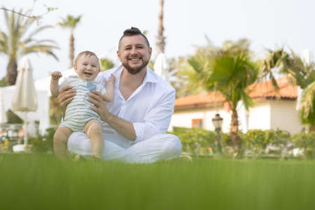 Happy father and his son sit on the grass - looking into the camera Stock Photo
