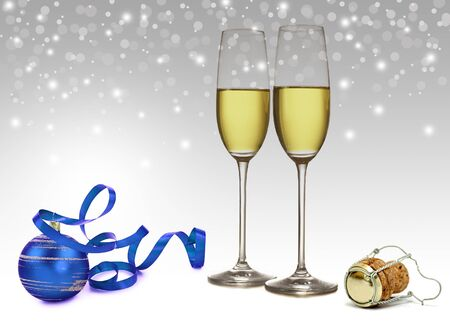 A blue Christmas tree ornament with ribbon, 2 champagne glasses and a champagne cork on a light and elegant white-grey bokeh background  Stock Photo