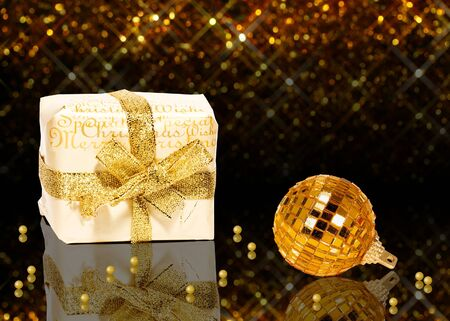 glitter ball: A glamourous golden Christmas illustration  A white gift box with golden christmas wishes, a golden Christmas ball and golden pearls on a noble dark and golden bokeh background  Stock Photo