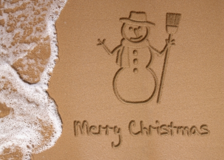 Sunny Christmas illustration  A snowman and Merry Christmas written in the sand on the beach next to the ocean