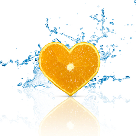 A heart shaped orange fruit with water splashes on a white background with reflection.