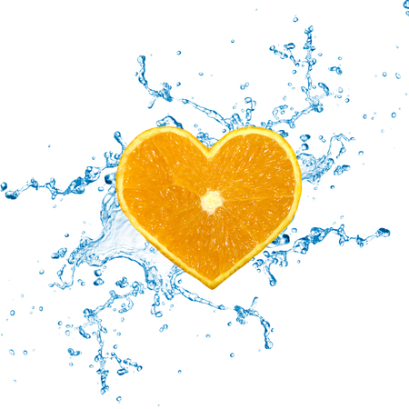 A heart shaped orange fruit with water splashes on a white background.