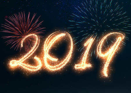 Happy New Year 2019 written with sparkle fireworks displayed on a dark night sky. Shiny bright glowing holiday illustration for New Years and seasons greetings.