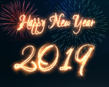 Happy New Year 2019 calligraphy written with sparkle fireworks displayed on a dark night sky. Shiny bright glowing holiday illustration for New Years and seasons greetings. Stock Photo