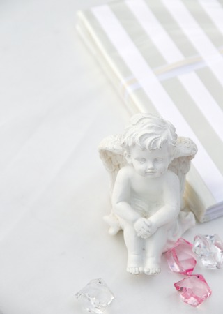 A little miniature statue of a white angel with wings on a white background Foto de archivo