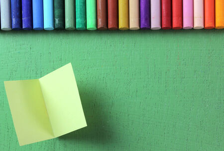 lined up: Crayons lined up in rainbow isolated on green , note pad
