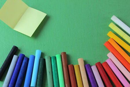 colors: Crayons rainbow isolated on green , note pad